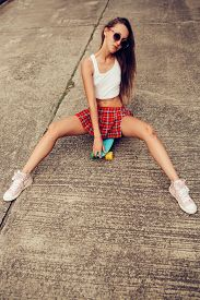 stock photo of mini-skirt  - Fit young woman in a sexy red tartan mini skirt sit on her blue penny skateboard longboard shortboard in the middle of the tropical street - JPG