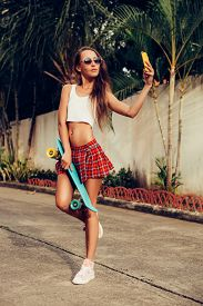stock photo of mini-skirt  - Sporty beautiful lady in a red tartan mini skirt with skateboard taking a selfie self portrait at the camera on her smartphone digital camera - JPG