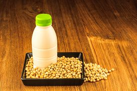 stock photo of soybeans  - Soybean and a bottle of soybean milk on wooden table - JPG