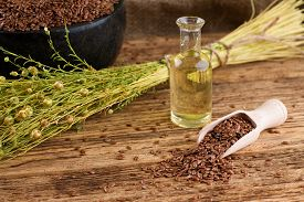 stock photo of flax seed oil  - Horizontal photo with wooden spoon full of flax seeds next to small glass bottle with flax oil and bunch of flax plants - JPG