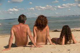 stock photo of naturist  - a Naked family sitting on the beach - JPG