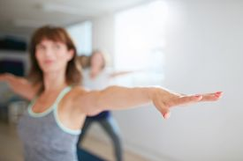 foto of virabhadrasana  - Woman stretching her arms at yoga class - JPG