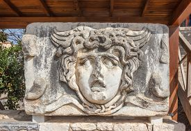 image of medusa  - Part of architrave with frieze with giant mythical Gorgon Medusa head in ancient Temple of Apollo in Didim Turkey - JPG