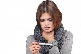 picture of temperature  - ill woman taking her temperature wile feeling sick and with fever - JPG