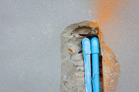 stock photo of mortar-joint  - bury a pvc pipe in the concrete wall with copyspace on the left - JPG