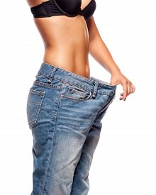 foto of big belly  - Close up of a woman belly in too big pants against white background - JPG