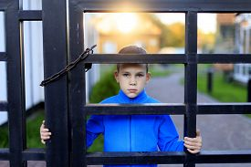 picture of punish  - Offended child stands behind a locked fence - JPG