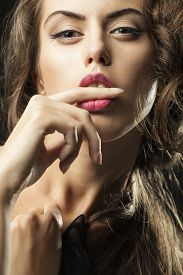 picture of big lips  - Portrait of one sensual young woman with big eyes pink lips and stylish haircut holding finger in open mouth looking forward closeup vertical picture - JPG