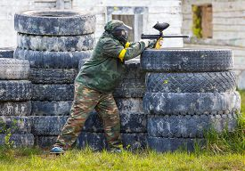 pic of paintball  - Paintball sportsman standing behind tires and shooting - JPG