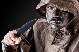 picture of army soldier  - a soldier wearing a poncho or raincoat and army camouflage face paint - JPG