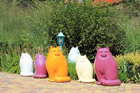 stock photo of nacked  - Multicolor ceramic cat statues in the garden - JPG