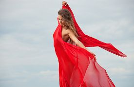 picture of nudist beach  - Beautiful nude woman with red fabric posing on sea beach against sky background - JPG