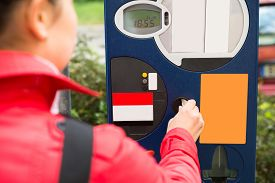 foto of insert  - Young Beautiful Woman Inserting Coin In Parking Meter - JPG