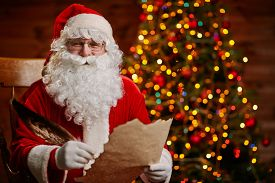 image of letters to santa claus  - Senior man in costume of Santa Claus holding feather and Christmas letter - JPG
