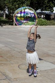 picture of hughes  - Three years old girl playing in the city with a huge bubble