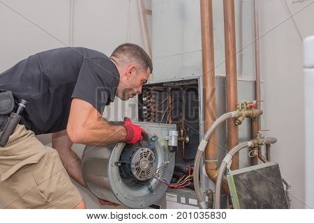 poster of Hvac repair technician removing a blower motor from air handler