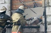 foto of firehose  - Firefighter with firehose spraying water in window of flaming house - JPG