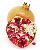 a pomegranate fruit cut in half and arils on a white background