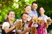 In Beer garden - friends in Tracht, Dindl and Lederhosen drinking a fresh beer in Bavaria, Germany