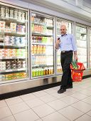 pic of grocery store  - Mature man looking at mobile phone while walking in front of refrigerators in shopping centre - JPG