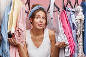 Female Model In Casual Clothes, Shrugging Her Shoulders While Standing Near Her Wardrobe, Having Hes poster