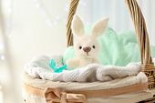 Cute knitted toy bunny in wicker basket poster