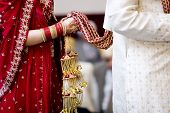 hindu bride walks behind husband holding garb