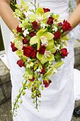 gorgeous orchid and roses bouquet, real flowers trailing over traditional white gown