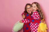 Girls In Colorful Polka Dotted Pajamas Hold Funny Pillows poster