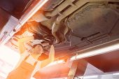 Low angle view of male automobile mechanic repairing car in repair shop poster