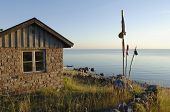 fishermens cottage with flags against sunset and sea
