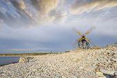 old windmill on stoney beach at sunset