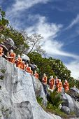 Statues of Buddhist Monks, queuing to take lotus flower offerings to Buddha, at the Rock Temple of Dambulla, Sri Lanka