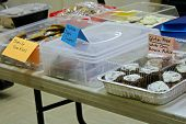 Items Set Up On A Table At A Bake Sale poster