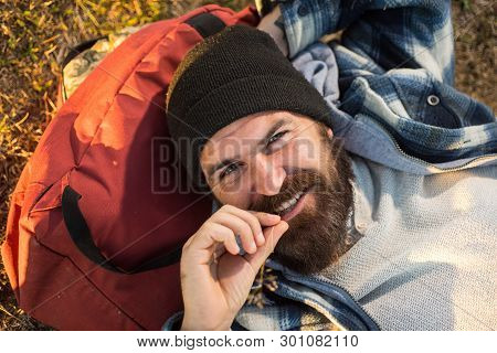 poster of Enjoying His Travel. Happy Travel Man With Long Beard Relaxing On Backpack. Bearded Hipster Smiling