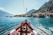 Boat Tour: Boat Bow, View Over Azure Blue Water, Village And  Mountain Range. Lago Di Garda, Italy poster
