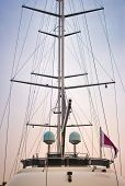 Mast Of A Luxury Sailing Yacht With Sails Down Showing The Rigging Against A Multi-colored Sky poster