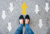 Woman Shoes On Asphalt And Opposing Direction Arrows On Asphalt Ground, Personal Perspective Footsie poster