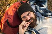 Enjoying His Travel. Happy Travel Man With Long Beard Relaxing On Backpack. Bearded Hipster Smiling  poster