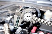 A shiny vernier caliper micrometer in front of a car engine during for servicing and repair