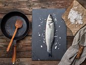 Fresh Whole Sea Bass Fish On A Black Graphite Board, Next To It Is An Empty Round Black Frying Pan O poster