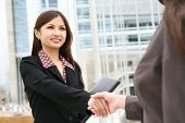 stock photo of asian woman  - A beautiful young asian business woman shaking hands - JPG