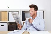 College student at desk reading job market section in newspaper