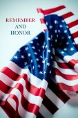 closeup of some flags of the United States of America and the text remember and honor written in the poster