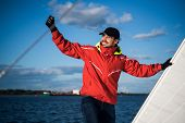 Young Man Skipper In Red Windbreaker And Black Cap Sets The Sails On A Sailing Yacht poster