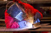 Welder In Red Overalls Creates Sparks.