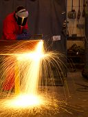 Welder Bends To Cut Metal Beam With Orange Sparks.