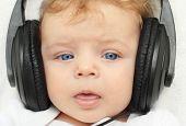 Happy baby boy 3 month old in earphones babbling