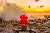 Tourist Woman Sitting On Bench Looking Sunset At Anse Kerlan, Praslin, Seychelles When Huge Powerful poster