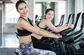 Group Of Young Asian  Fitness Woman In Sportswear Exercising With Biking In Sport Gym Club . Two Gir poster